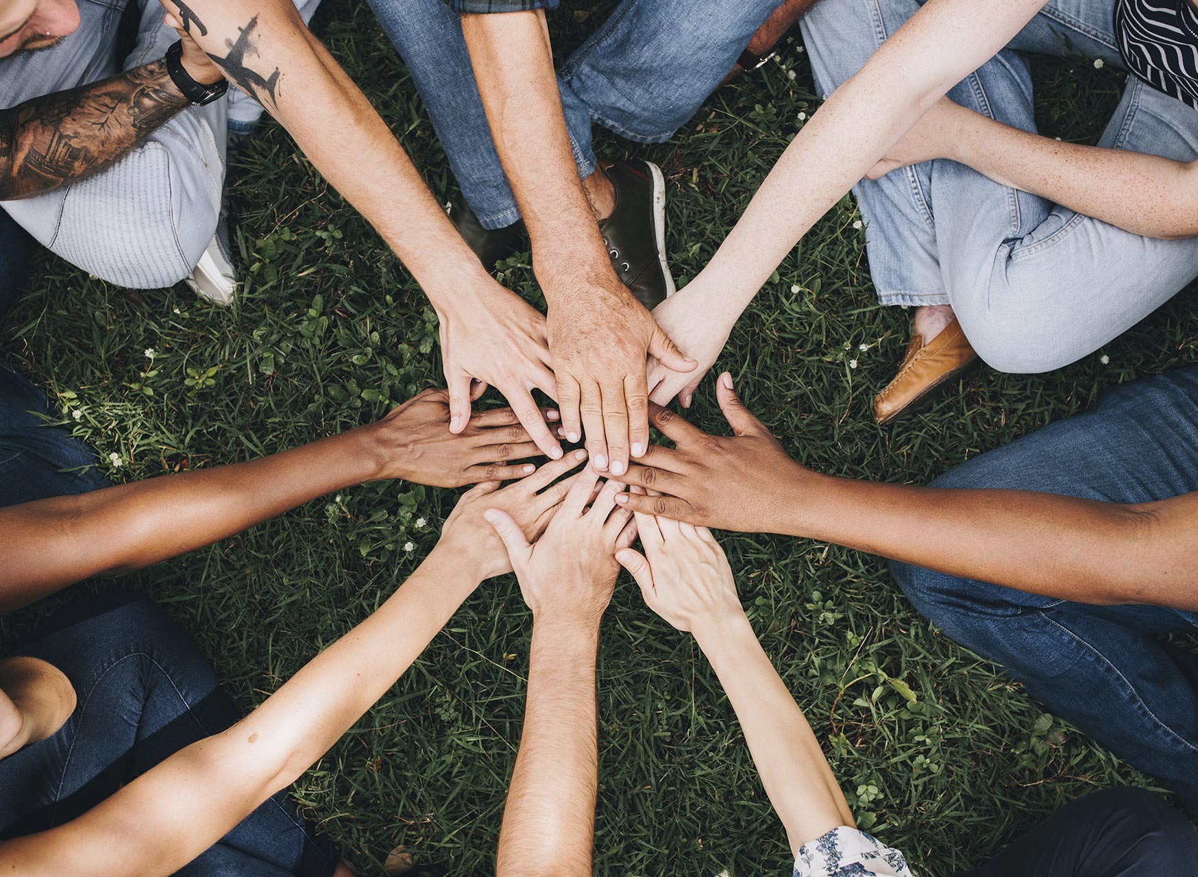 people-stacking-hands-together-in-the-park